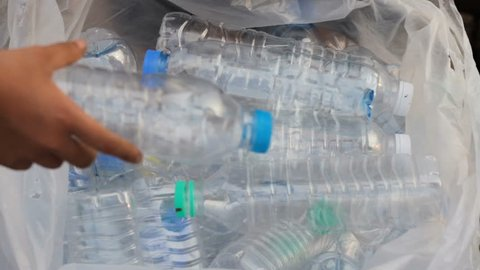 Group of volunteer put a plastic bottle that picking up around the river, beach in to the bag