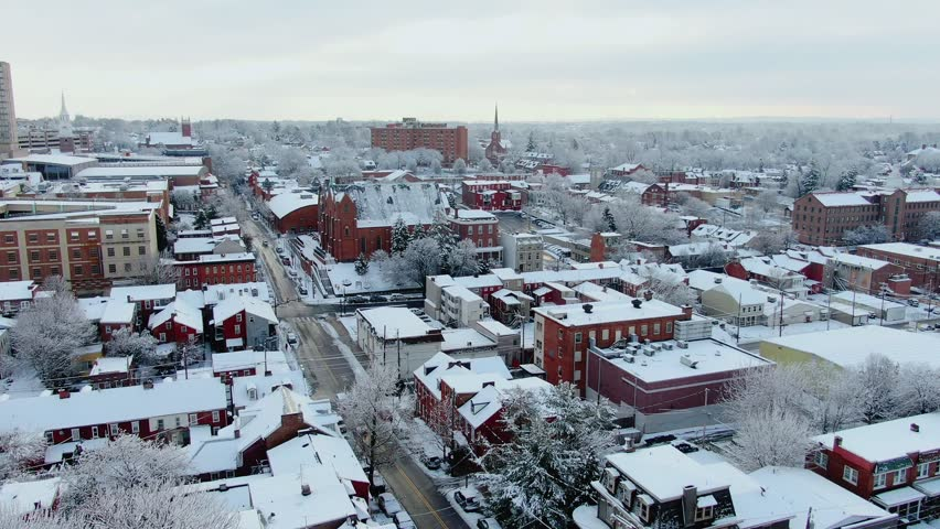 Winter morning in a small American town on the East Coast, trees and roofs of buldings covered in fresh layer of snow, steeples and multi story buldings dominate the skyline, Lancaster, Pennsylvania