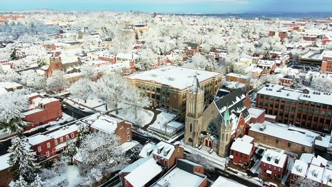 Aerial view of downtown Lancaster, Pennsylvania in winter with St. John's Lutheran church and Fulton elementary, cityscape in background covered in snow