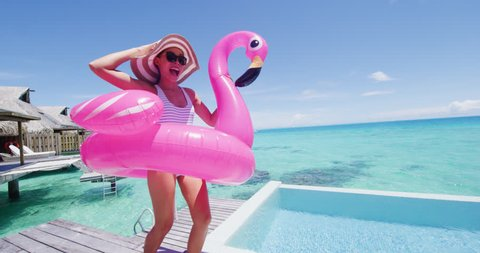 Funny vacation woman in bikini with inflatable pink flamingo pool toy mattress by swimming pool. Girl laughing having fun sunbathing enjoying travel holidays at resort luxury overwater bungalow travel