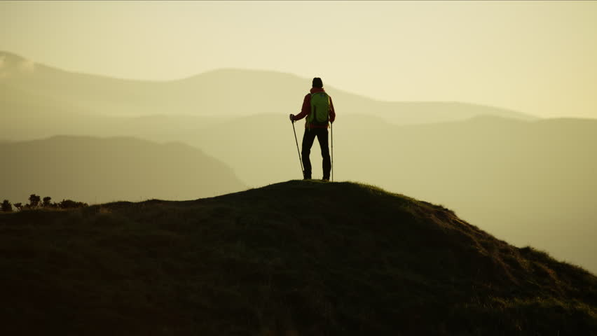Silhouette of Caucasian European female adventure hiker on her vacation hiking mountain at sunset Snowdonia National Park Wales RED MONSTRO | Shutterstock HD Video #1028325593