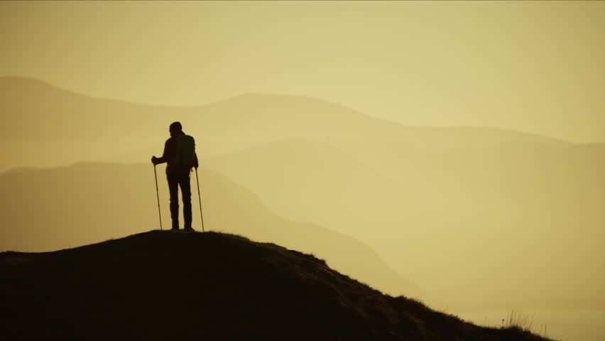 Silhouette of fit Caucasian European female hiker Nordic walking mountains outdoors at sunset dusk Snowdonia National Park Wales RED MONSTRO #1028326373