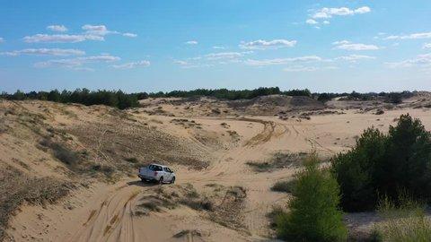 Ukraine, Oleshkivski pisky. 21 april 2019 - Mitsubishi L200 off road pickup truck driving on sand in desert. Aerial view