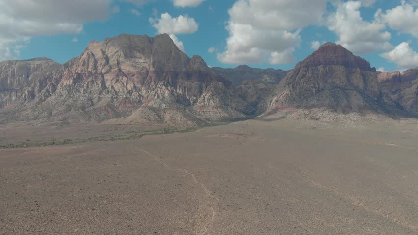 4K resolution, aerial drone at 24 frames per second over mountains in Red Rock Canyon National Park outside Las Vegas, Nevada with cloudy skies (speed ramped / fast forward / sped up) | Shutterstock HD Video #1028344493