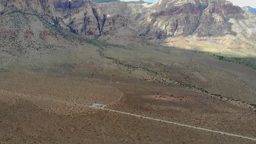 4K resolution, aerial drone at 24 frames per second over mountain in Red Rock Canyon National Park and Desert outside Las Vegas, Nevada with cloudy skies (speed ramping / fast forward / sped up) | Shutterstock HD Video #1028344823