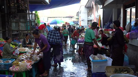 UBUD, BALI, INDONESIA - APRIL 25, 2019 : Poor Indonesian people selling and buying healthy food at the morning market in village Ubud, island Bali, Indonesia. Early morning fruit and vegetable market