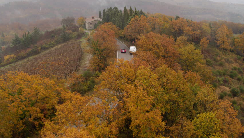 Aerial view of a vintage red convertible sports car driving along a quiet road in rural Tuscany, Italy. 4k aerial
