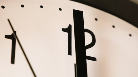 Black and white clock face approaching 12 o'clock