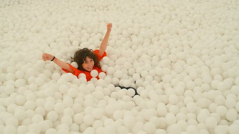 A cute 9-10 years old girl having fun among lots of white ball in a ball pit. 4k slow motion