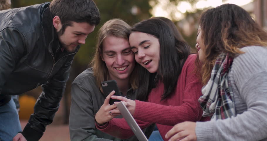 Students working on a laptop computer stop to take a selfie with a smart phone outside on a university campus #1028453183