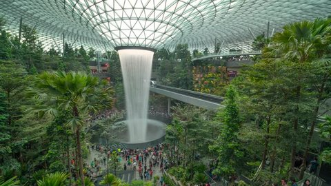 SINGAPORE APR 2019: time lapse clip of Tourists enjoying rain vortex attraction in Changi Jewel airport, Singapore