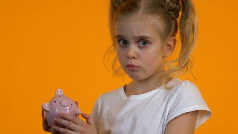 Upset female child shacking empty piggy bank, poor personal budget lack of money