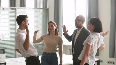 Happy leader motivate diverse employees business team give high five together, excited office workers group and coach engaged in teambuilding celebrate success good results reward in teamwork concept