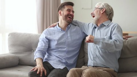 Happy generations old father laughing embracing young son giving fist bump sit on sofa at home, friendly senior dad hug adult man talking joking having fun enjoy time together and good relationships