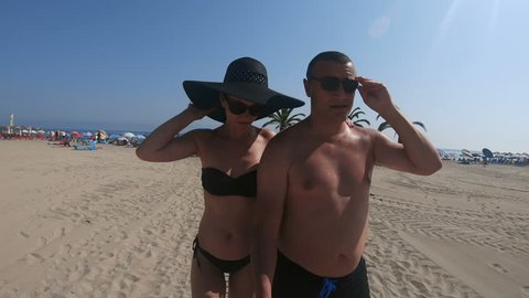 Selfie of couple walking on beach. Young happy interracial couple walking on beach smilin