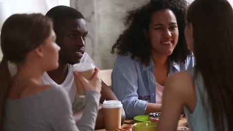 Diverse students multi-ethnic group of best friends sitting round the table in cafeteria chatting hanging out spending weekend, friendship between multi-racial adolescent, good warm relations concept
