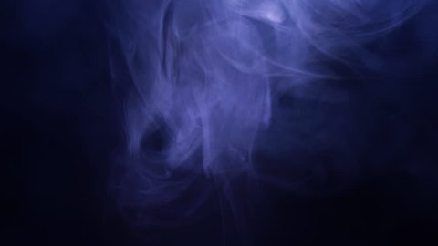 Smoke in slow motion on black background. Color smoke slowly floating through space against black background.