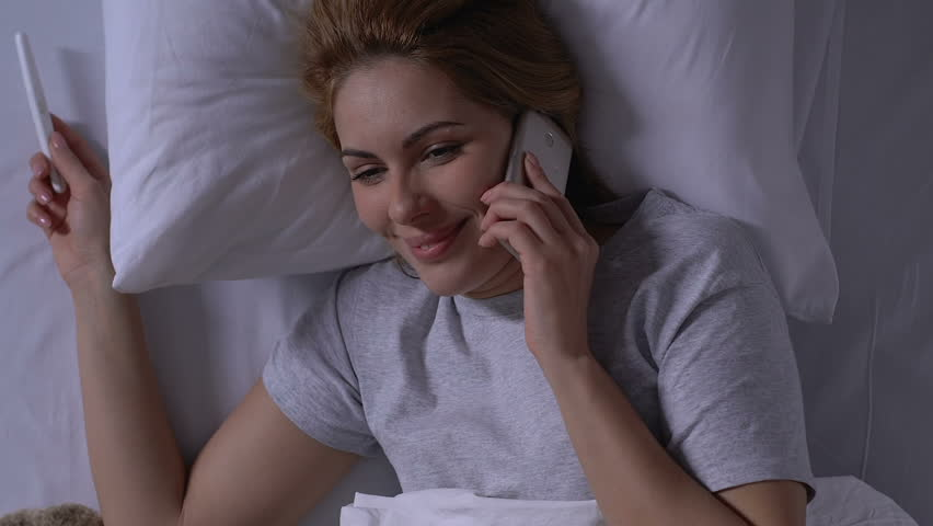 Smiling woman in bed holding pregnancy test and talking phone, positive result #1028591903