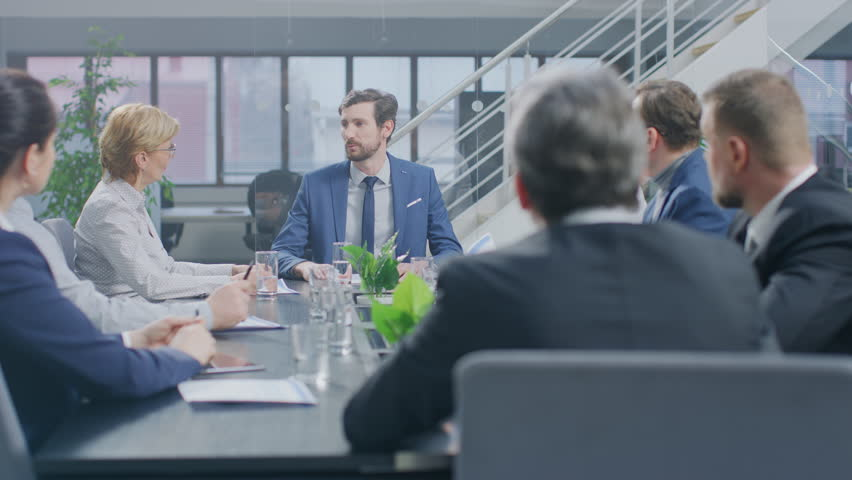 In the Corporate Meeting Room Close-up on the Hands of Businesspeople, Signing Contracts, Using Smartphones and Digital Tablet Computers, Gesticulating. People Sitting at Conference Table   Shutterstock HD Video #1028612423