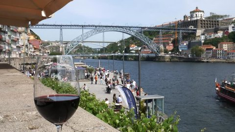 Porto, Portugal - April 29, 2019: Red Porto wine glass overlooking tourists at Cais da Ribeira and Ponte de Dom Luis I on the River Douro in Porto, Portugal. Live accoustic guitar music - 4K