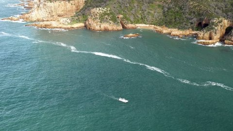 High angle of blue water river mouth, rocky cliffs shoreline with caves and a small power boat moving up stream, white lines of foam on water surface, sunny,  Knysna, South Africa
