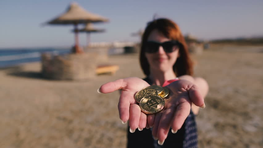 Bitcoin. Girl throws Bitcoin coins on the background of the beach