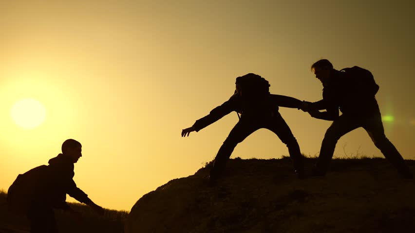 teamwork of business people. Climbers silhouettes stretch their hands to each other, climbing to top of hill. travelers climb one after another on rock. joint business. Slow motion #1028719823