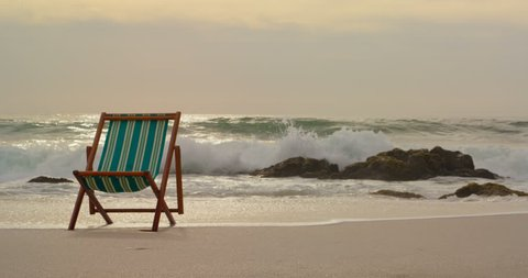 Front view of a green and brown wooden sun lounger on the beach with waves at the back