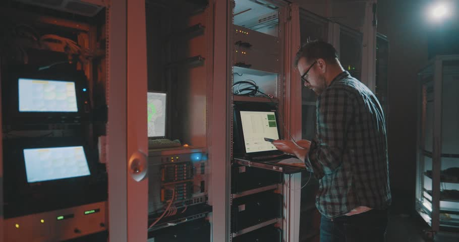 Male caucasian programmer connects smartphone to laptop while working as system admin with server in data center | Shutterstock HD Video #1028761643