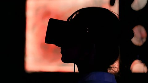Woman using virtual reality headset and looking around at interactive technology exhibition. VR, augmented reality, digital art, futuristic, interactive, immersive and entertainment concept