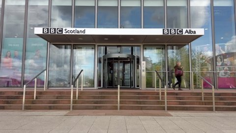 GLASGOW, UK - MAY 2, 2019: An employee exits via the front entrance of BBC Scotland's public service broadcast headquarters located at BBC Pacific Quay on the banks of the River Clyde in Glasgow, UK.