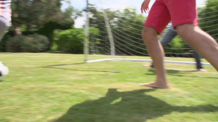 Grandson playing football with father and grandfather - he scores goal.Shot on Sony FS700 at frame rate of 25fps