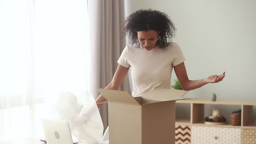 Shocked frustrated african american woman customer open cardboard box receive damaged wrong parcel, annoyed black girl consumer having problem with bad shopping order dissatisfied with post shipping