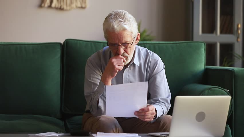 Serious old retired man holding paper calculating domestic bills at home using calculator laptop, senior aged grandfather counting household payments to pay online on computer sitting on sofa alone