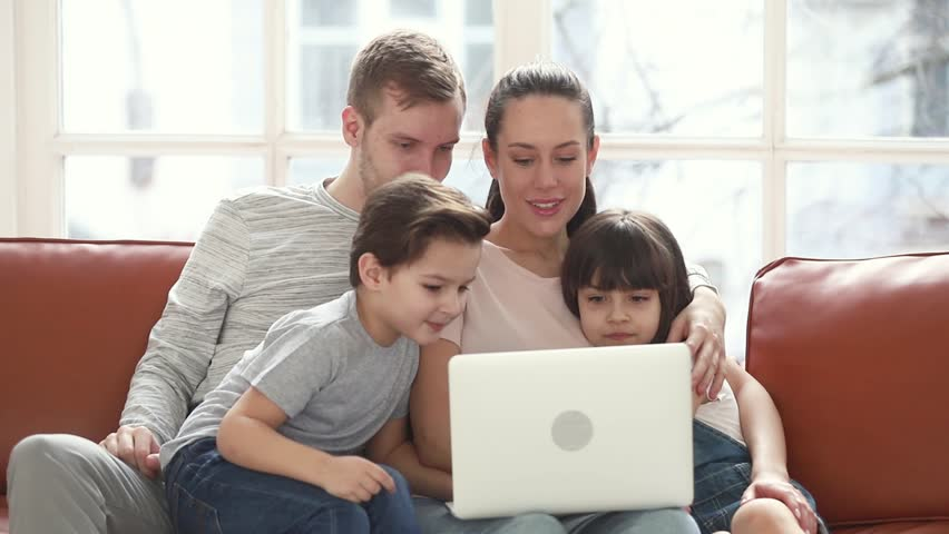 Happy family of four mom dad and little children having fun with laptop looking at screen sit on sofa together, parents teaching kids using computer apps online enjoy spend time with device at home