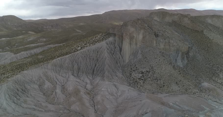 Flying towards eroded mountain slope from general front view to senital detail of strange water erosion formations. Abstract drawings. Coranzuli, Salta, Argentina | Shutterstock HD Video #1028910563