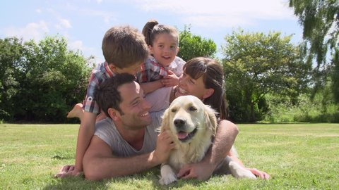 Family piled up on grass in garden with pet golden retriever.Shot on Sony FS700 at frame rate of 25fps