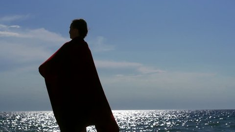 Silhouette of an adult successful woman on vacation against the sea with a large handkerchief in the wind. Slow motion