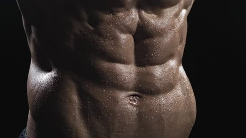Close-up of abs of unrecognizable shirtless muscular man.  Muscle man posing on a black background, shows his muscles. The concept of bodybuilding