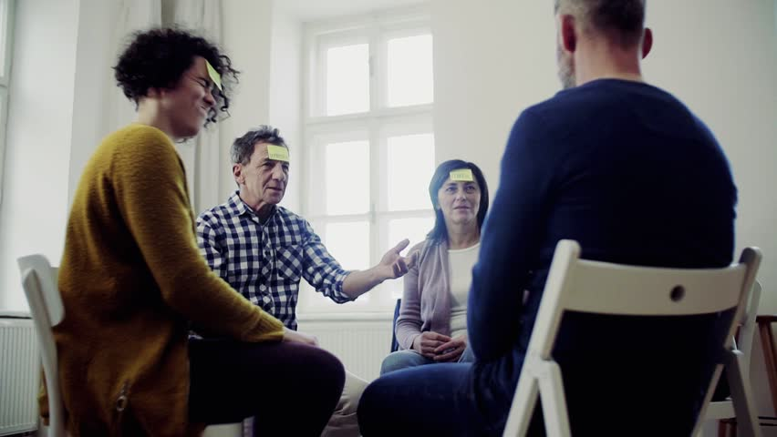 Men and women sitting in a circle during group therapy, adhesive notes on forehead. | Shutterstock HD Video #1029014843