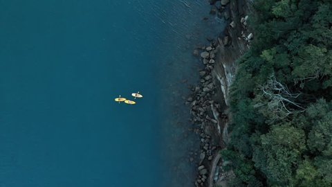 Aerial: Three People Kayaking in Vibrant Tropical Water Near Rocky Coastline in Ilhabela, Brazil