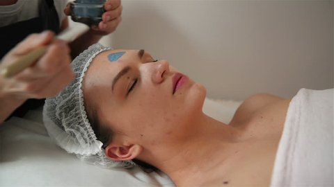 Cosmetologist Makes Procedure Of Cleansing And Moisturizing Of skin. Applying Mask With Special Brush To Face Of Woman. Young Girl Takes Care Of Her skin. Visits Cosmetology Clinic. Aethetic Medicine.