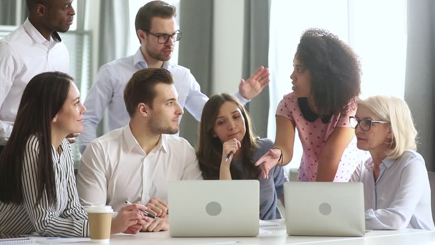 Diverse office workers team gather talking discussing online project laugh working together at corporate group business meeting, multiracial employees involved in teamwork in workplace with laptops | Shutterstock HD Video #1029051473