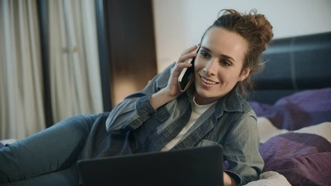 Happy woman talking mobile phone at evening home. Portrait of smiling woman call phone at night. Cheerful person lying with mobile on bed. Joyful woman talking phone at home