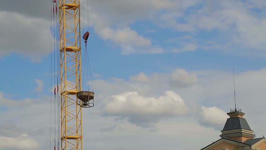 Tower crane raises and lowers materials for construction work on the building