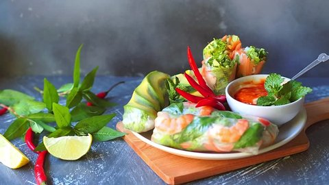 Rice paper rolls or summer rolls with shrimp,vegetables and avocado dip in spicy mayo sauce by hand, Vietnamese food.