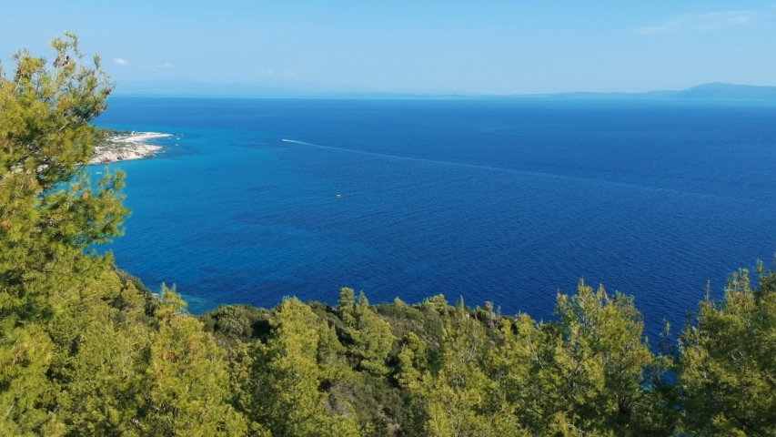 Mediterranean Coast With Pine Forest and Deep Blue Sea Water. Aerial View Of The Blue Water Coast Line, Sithonia Peninsula, Halkidiki,Greece. Drone Descending Over Pine Trees With Blue Sea Background. | Shutterstock HD Video #1029196103