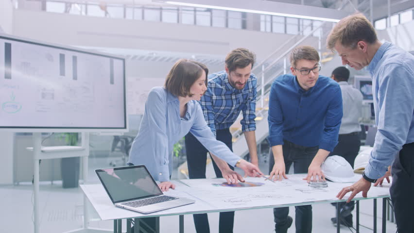 In the Industrial Engineering Facility: Diverse Group of Engineers and Technicians on a Meeting Gather Around Table with Engine Design Technical Drafts, Have Discussion, Analyse Technology   Shutterstock HD Video #1029209423