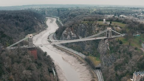 Aerial shot of the Clifton suspension bridge circling around over the River Avon, Bristol, during overcast cloudy day. Filmed on DJI Mavic 2 Pro