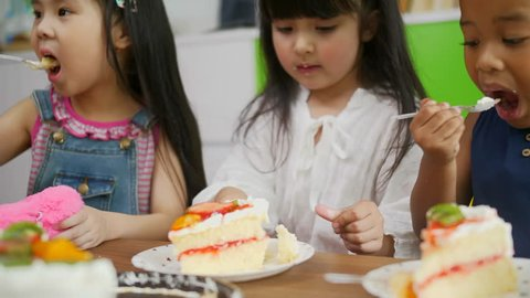 African American little girl and friends are eating a sweet fruit cake, her face is smeared with whipped cream from cake, kids enjoy eating birthday cake So yummy.